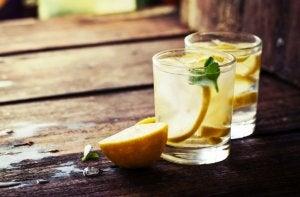 To glass vann med sitron på trebord.