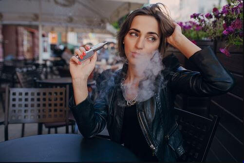 kvinne røyker e-sigarett