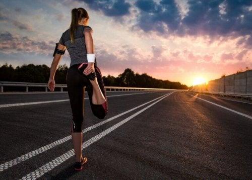 kvinne strekker ut før hun løper