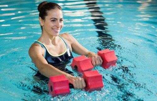 Kvinne holder vekter i bassenget