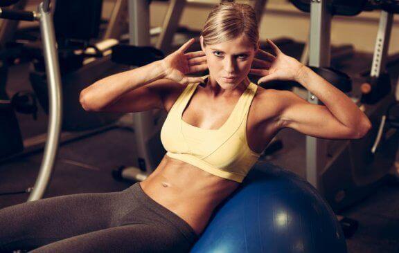 Kvinne trener magemuskler med medisin ball