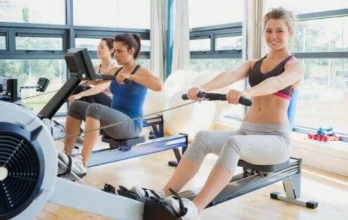 Kvinner trener på romaskiner