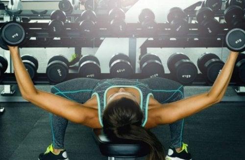 En dame som trener brystmusklene.