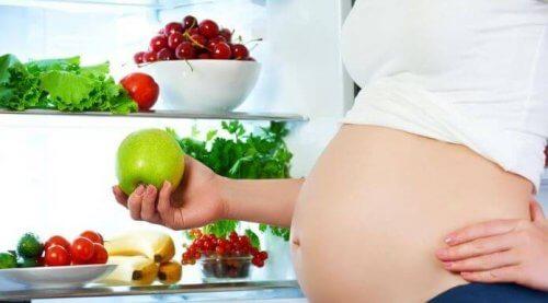 gravid kvinne spiser frukt og grønnsaker