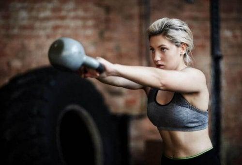 Kvinne som trener med kettlebells.