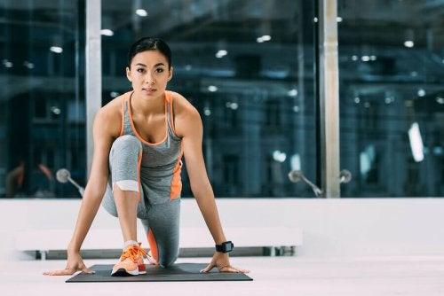 kvinne tøyer ut stramme hoftefleksorer på treningmatte