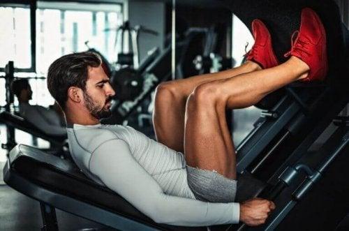 En mann trener bena på et treningsstudio