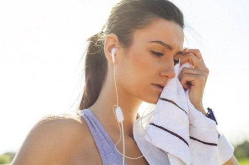 kvinne tørker av seg svette