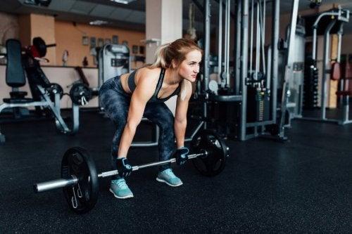 kvinne trener markløft for å løfte mer vekt på treningssenteret