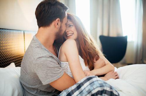 Mann og kvinne sitter i sengen