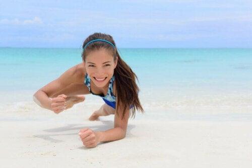 Kvinne trener på stranden