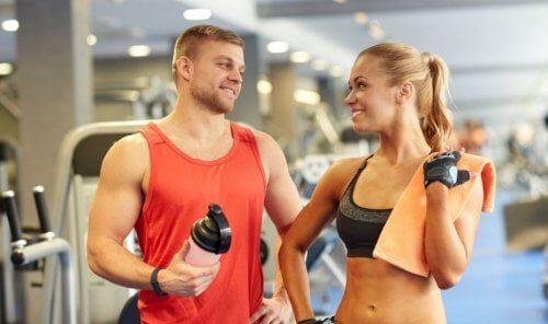 En mann som snakker med en kvinne og holder en proteinshake