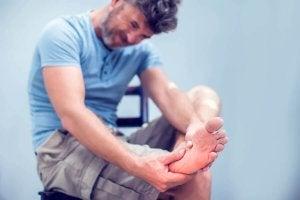 En mann som masserer en smertefull krampe i foten.