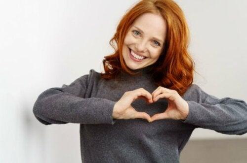 Kvinne symbolerer et hjerte med fingrene