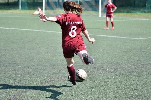 En jente som sparker en fotball.