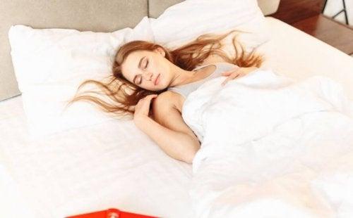En kvinne som sover i sengen sin.