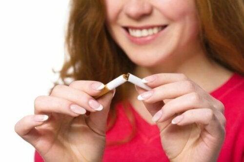 Kvinne som bryter en sigarett for å sove bedre.