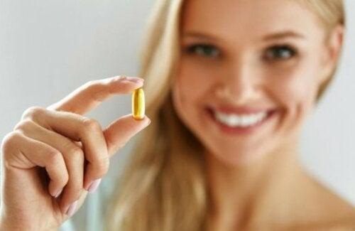 Kvinne som holder en kapsel med Omega-3.
