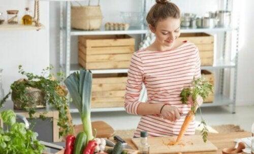 Kvinne som skjærer en gulrot på kjøkkenet.