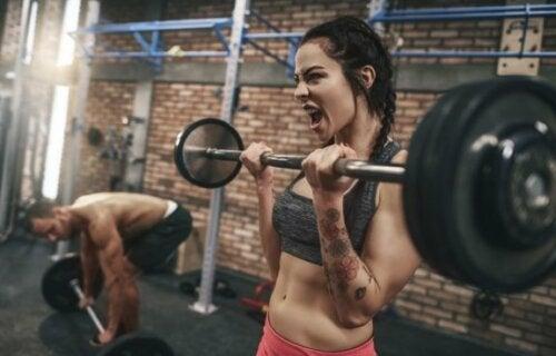 Kvinne trener med vektstang for å bygge muskler.