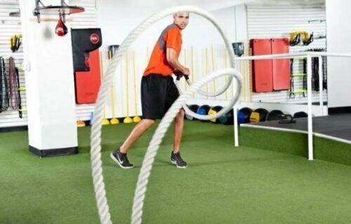 Mann som gjør bevegelser med treningstau.