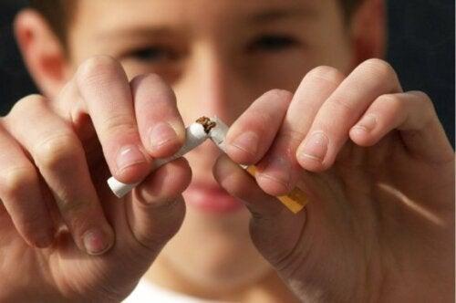 Gutt knekker en sigarett i to