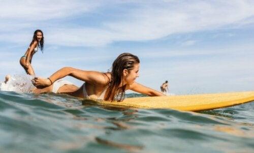 Jenter surfer i havet
