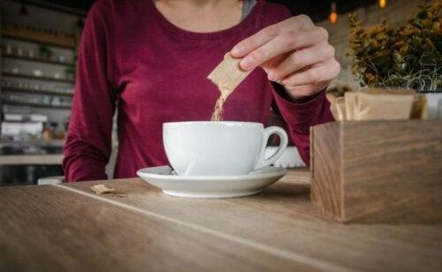 Kvinne tilsetter sukker i kaffen