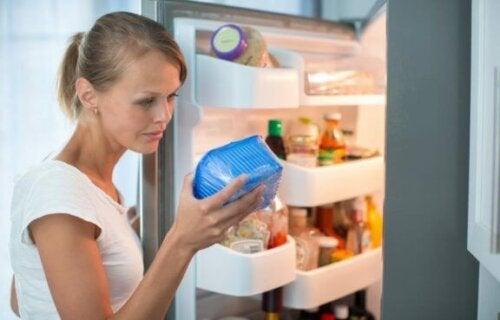 En kvinne sjekker holdbarheten på mat i kjøleskapet.