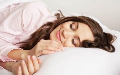 En kvinne som smiler mens hun sover