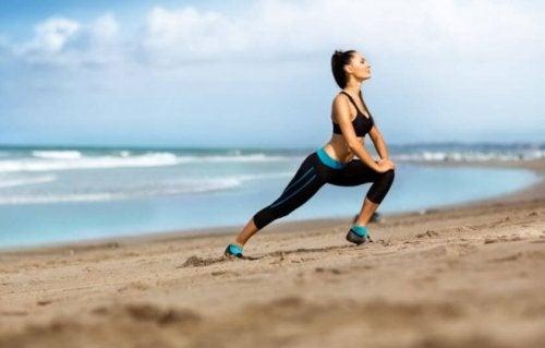 En kvinne som tøyer ut på stranden