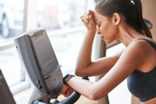 Kvinne med muskelutmattelse som prøver å trene.