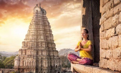 Kvinne som mediterer foran et tempel