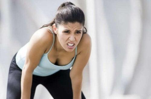 En kvinne som er sliten etter intens trening med en ordentlig oppvarming for å unngå muskelstrekk