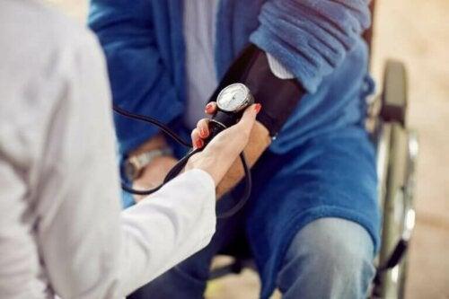 En lege som måler blodtrykksnivået til en hypertensiv person for å se om de kan komme i gang med idrett