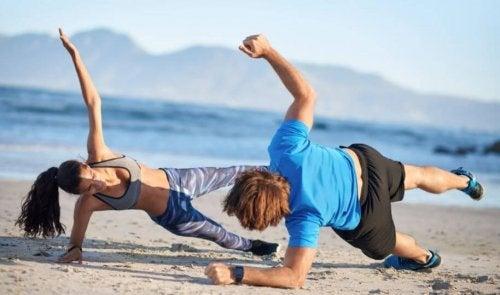 Par som gjør øvelser på stranden.