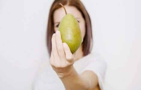 En kvinne som holder en pære for å vise en av de beste fruktene å spise om sommeren