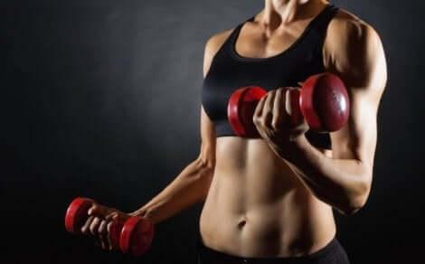 En kvinnelig idrettsutøver som løfter vekter for å forbedre kroppssammensetningen