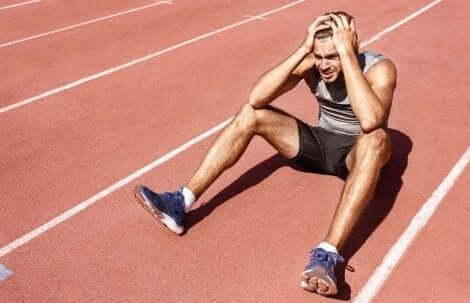 En løper som sitter på bakken og holder seg på hodet