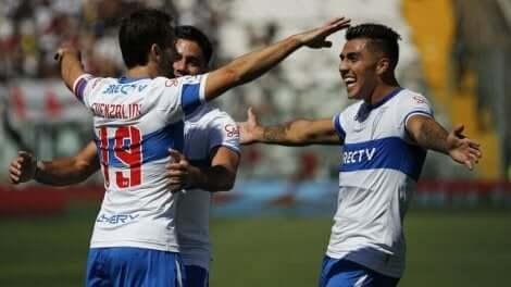 Tre spillere fra Universidad Catolica-laget som klemmer etter å ha vunnet et av de klassiske møtene i chilensk fotball