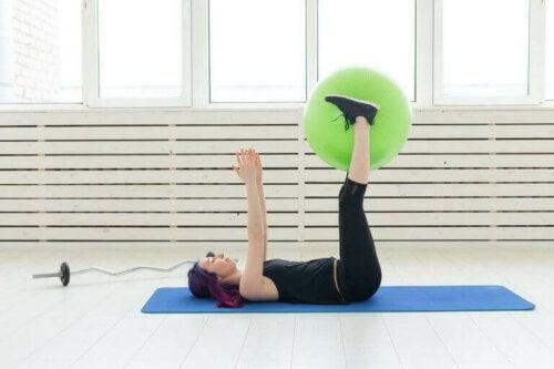 Kvinne ligger på gulvet med en fitnessball mellom føttene