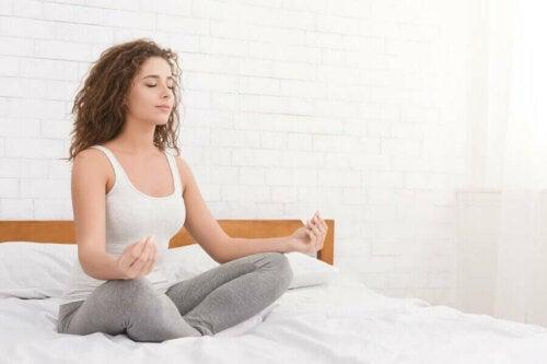 Kvinne mediterer på sengen