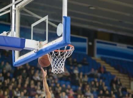 en hånd som skyter en basketball opp mot kurven