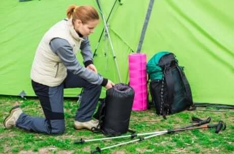 kvinne som pakker sammen soveposen sin i et telt
