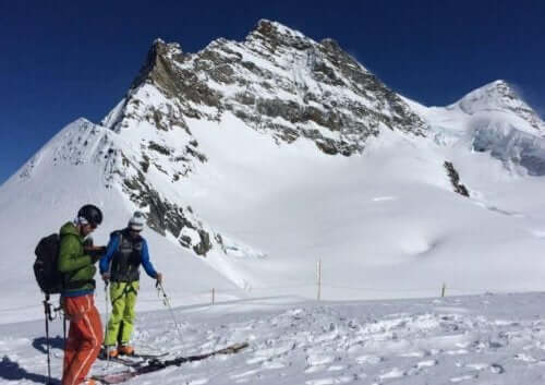 menn som står på ski på fjellet