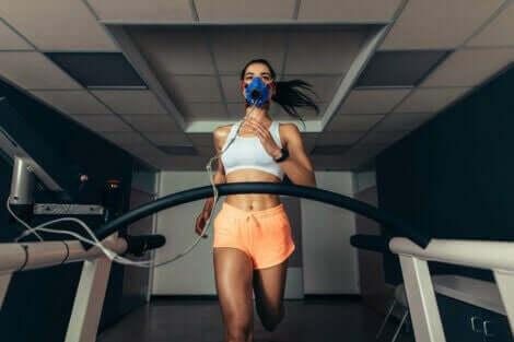 En jente som løper på tredemølle med en oksygenmaske