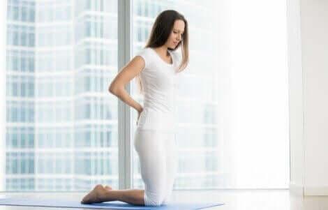 En kvinne på en yogamatte som har hendene på korsryggen.