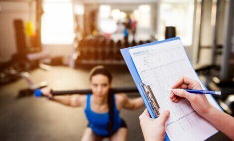 En kvinne som trener mens noen andre holder oversikt.