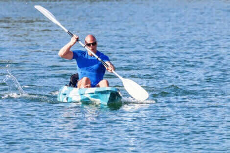 En mann padler kayakk i åpent farvann.