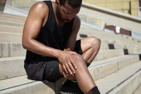 En mann som holder rundt kneet sitt etter å ha lidd en kneskade.